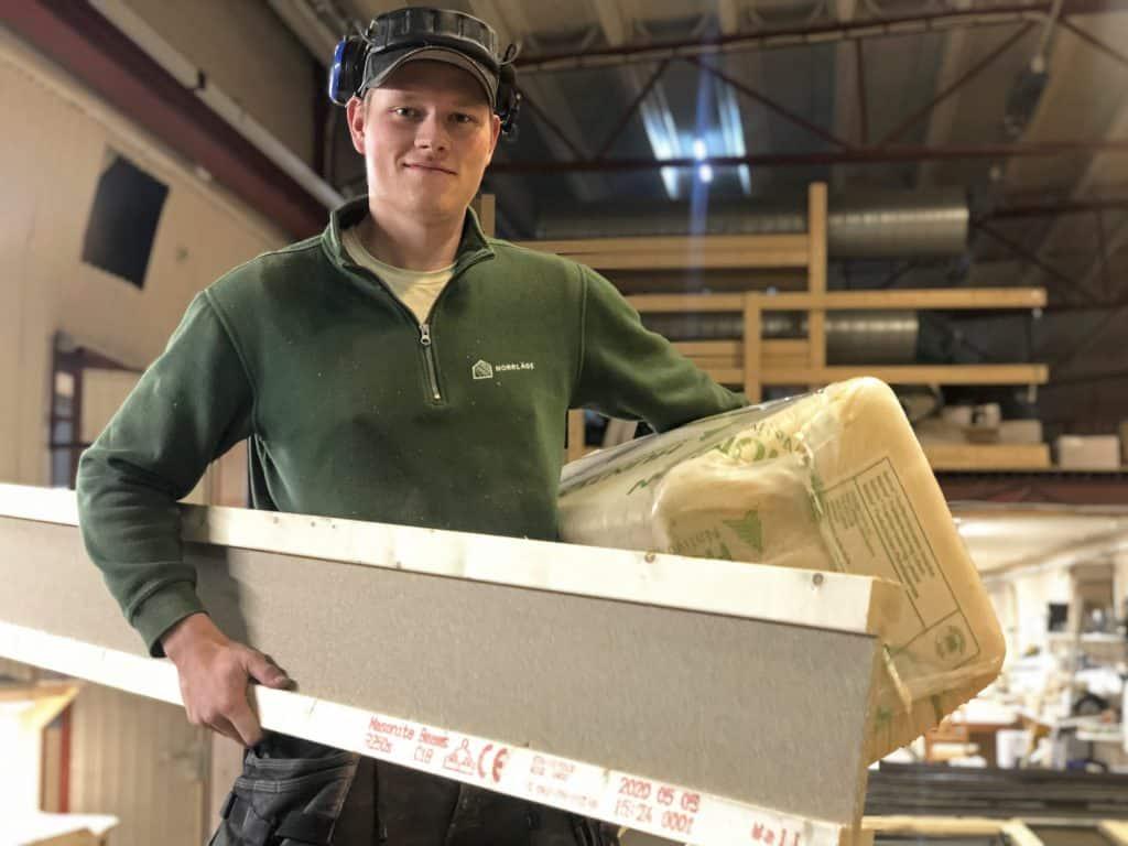 Snickaren Carl Fägerman i husfabriken med vad som ska bli den nya miljöväggen - lättviktsbalk från Masonite Beams och Hunton's träfiberisolering.